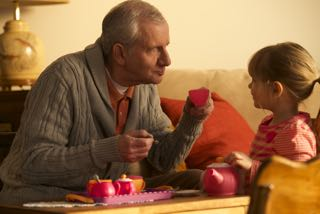 """grandfather having """"pretend tea"""" with his granddaughter"""